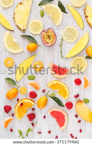 Collection of fresh whole and sliced yellow, orange and red fruits on white rustic background. Still life pattern background. Overhead view - stock photo
