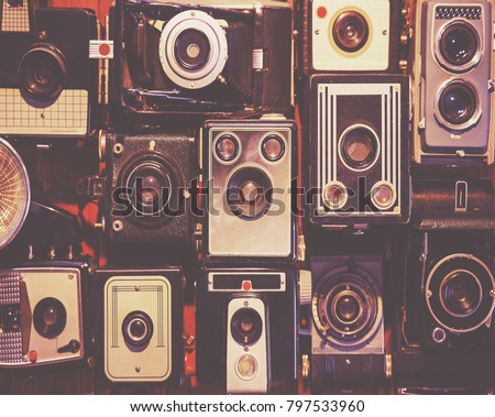 collection of generic antique box cameras on a wooden floor with dramatic lighting toned with a vintage retro instagram filter effect app or action