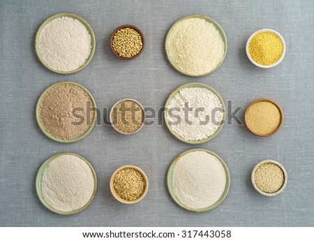 Collection of gluten free grain and flours in small bowls. Left from top buckwheat, teff, rice. Right from top millet, amaranth, quinoa - stock photo