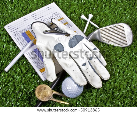 Collection of golf equipment resting on green grass - stock photo