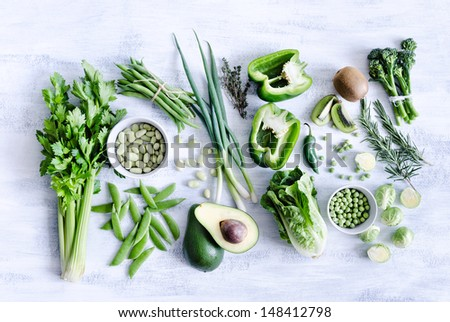 Collection of green produce from farmers market on rustic white background from overhead, broccoli, celery, avocado, brussels sprouts, kiwi, pepper, peas, beans, lettuce, - stock photo