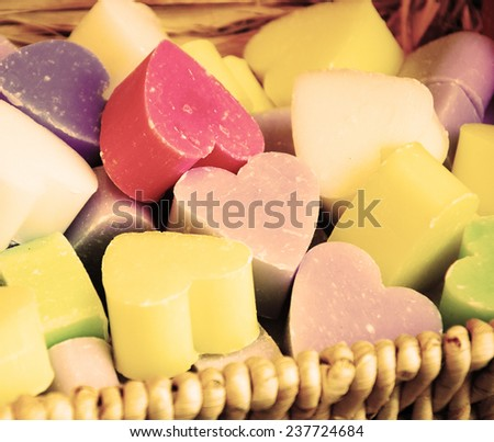 Collection of heart shaped soaps in wicker basket . Aged photo. - stock photo