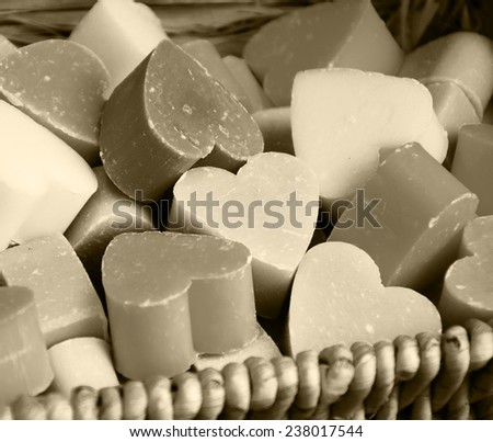 Collection of heart shaped soaps in wicker basket . Aged photo. Sepia. - stock photo