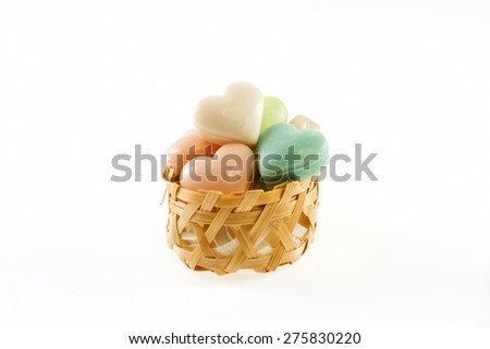 Collection of heart shaped soaps in wicker basket isolated on white background - stock photo