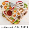 Collection of herbs and spices on a wooden background with heart-shaped - stock photo