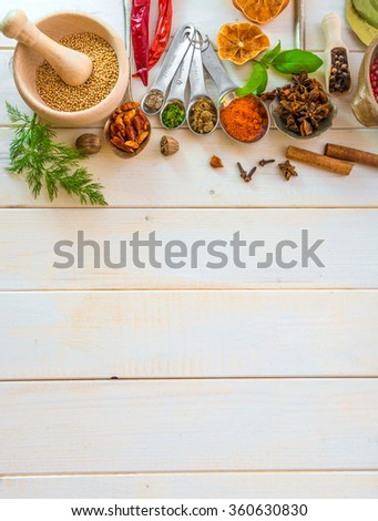 Collection of herbs and spices on a wooden background with space for text