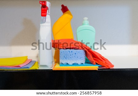 Collection of household cleaning supplies displayed on a kitchen counter with a sponge, gloves, cloths and spray bottles - stock photo