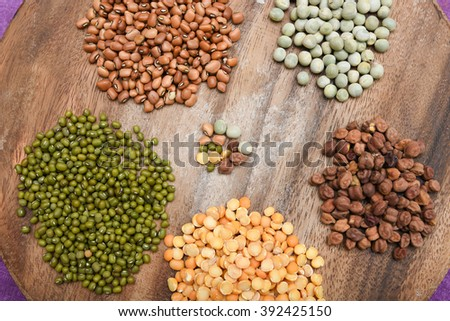 Collection of Lentils, beans various colors on wooden base/ table as background, top view Kerala, India. legumes chickpeas, green lentils, green mung, pulse, rice and dal/ dhal - stock photo