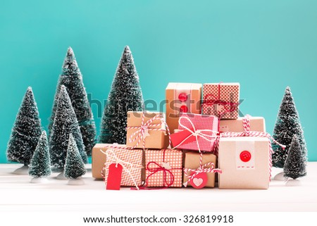 Collection of little handmade gift boxes in a snow covered miniature evergreen forest - stock photo