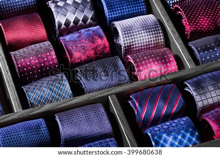 collection of luxury neckties on black wooden showcase, macro photo and copy space