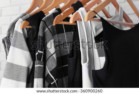 Collection of male and female clothes hanging on a rack - stock photo