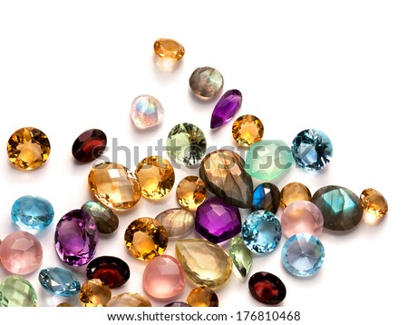 Collection of many different natural gemstones on the white background: amethyst, lapis lazuli, rose quartz, citrine, ruby, amazonite, moonstone, labradorite, chalcedony, blue topaz and many more. - stock photo
