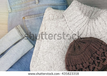 Collection of men's warm autumn clothes on a light wooden background. Knitted sweaters, jeans and beanie hat. Set of winter fashion clothes. (Color Process)  - stock photo