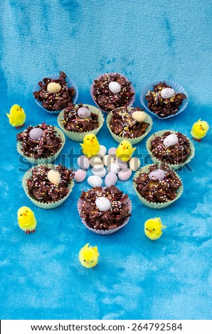 Collection of mini chocolate Easter eggs, cornflake cakes and baby chicks - stock photo