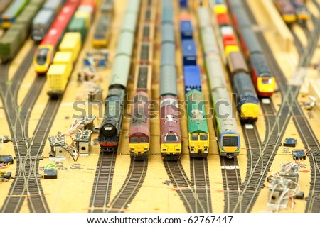 collection of model trains in an unfinished replica station - stock photo