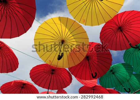 Collection of multi colored umbrellas hanging up in an open position over a street
