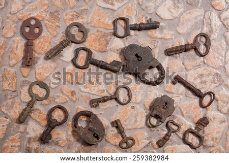 collection of old keys on stone floor - stock photo