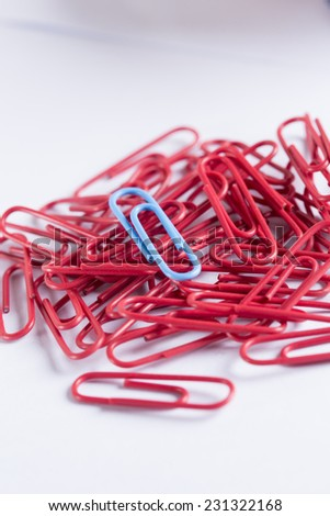 collection of paperclips in various colours on white with stationary items - stock photo