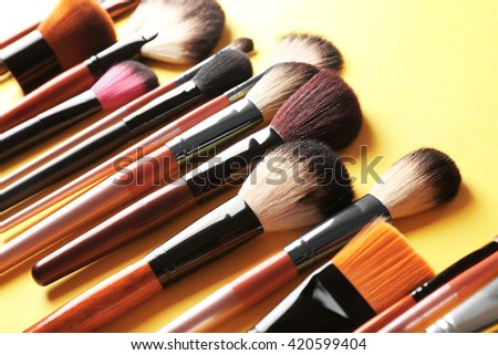 Collection of professional makeup brush on yellow background