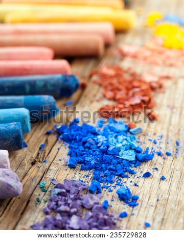 Collection of rainbow colored pastel crayons with crushed chalk on old wooden desk. - stock photo