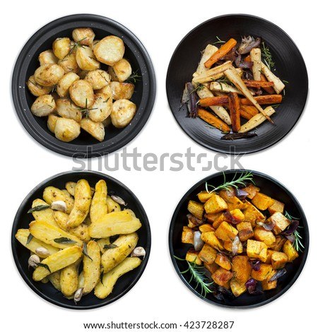 Collection of roasted vegetables on black platters, isolated on white.  Includes potatoes, kumara, parsnips and carrots.