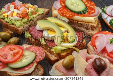 Collection of sandwiches on wooden table  - stock photo