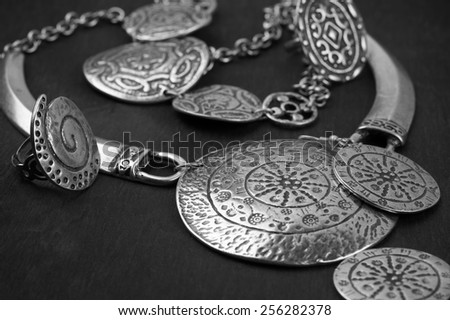 Collection of silver ethnic jewelry on black wooden background.