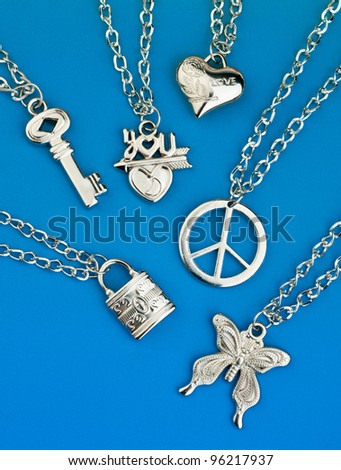 collection of silver pendants on the chains - stock photo