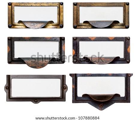 Collection of six old, tarnished brass file drawer label holders and drawer pulls with blank cards. Isolated on white. Includes clipping path. - stock photo