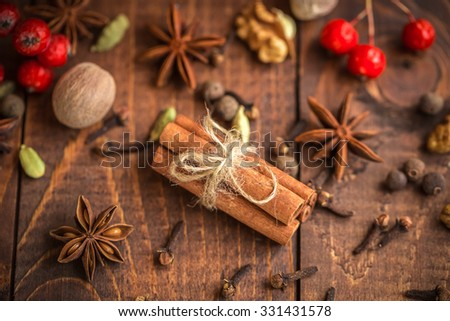 Collection of spices for mulled wine and pastry on the wooden table - stock photo