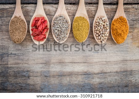 Collection of spices on a wooden spoon - stock photo