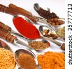 Collection of spices on wooden spoons isolated on white - stock photo