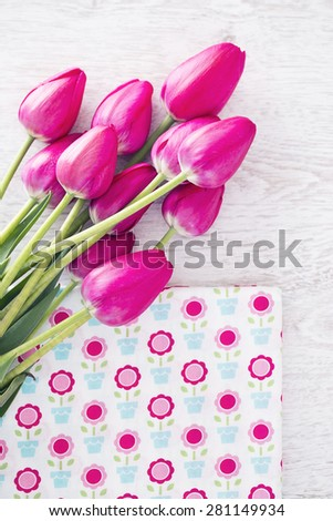 Collection of spools  threads in pink colors arranged on a white wooden table - stock photo