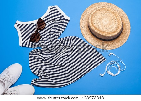 Collection of summer clothes and accessories for a young woman on blue background