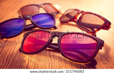 Collection of sunglasses on wood background
