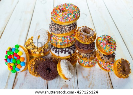 Collection of tasty donuts on white wooden board - stock photo
