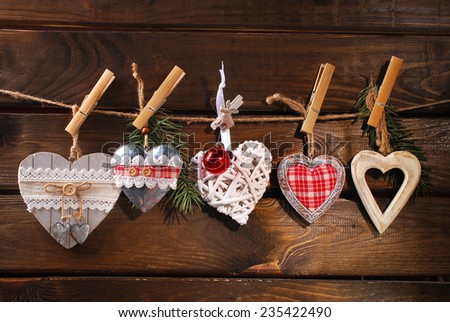 collection of various christmas hearts hanging on twine against wooden background - stock photo
