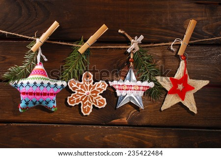 collection of various christmas stars hanging on twine against wooden background  - stock photo