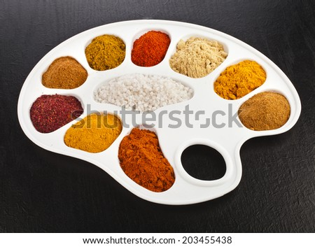Collection of various colorful spices on a cooking palette on black wooden surface table - stock photo
