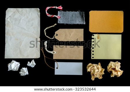 collection of various grunge paper pieces and tag isolated on black background
