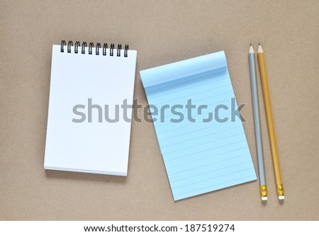 Collection of various note paper and pencils on brown background.