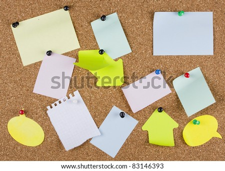 collection of various note papers on an corkboard - stock photo