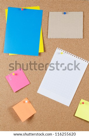 collection of various note papers on corkboard - stock photo