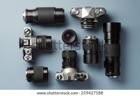 Collection of vintage cameras and camera lens well organized over blue background, top view - stock photo