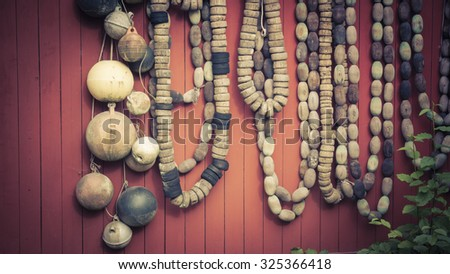 Collection of vintage fishing floats hung on a red wall with vintage coloration. - stock photo