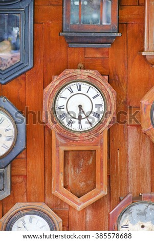 Collection of vintage wood Clocks on wood wall background - stock photo