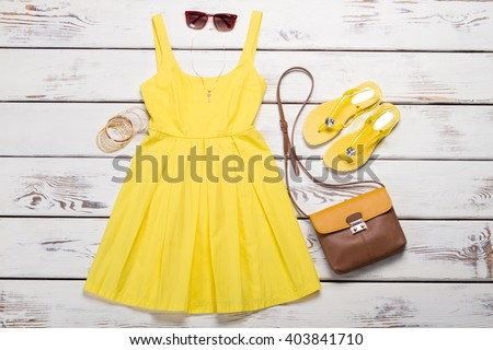Collection of women's summer clothes. Yellow bright dress with accessories on wooden background. - stock photo