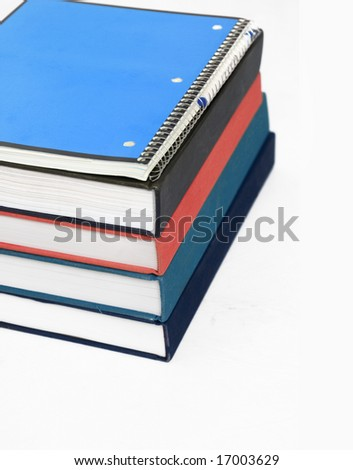 Collection or stack of text books with spiral bound note pad and pen sitting on top - stock photo