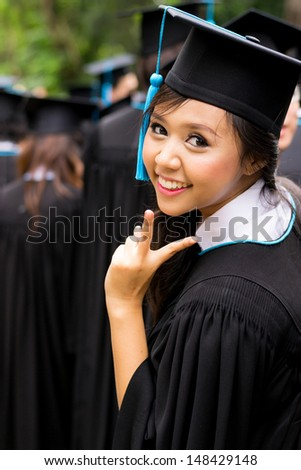 College degree. Happy young women in robe