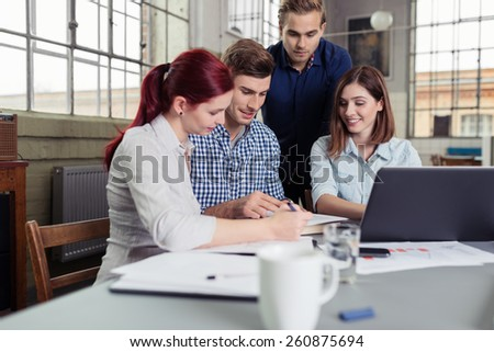 College Friends Having Serious Group Study at the Table Inside the Office. - stock photo
